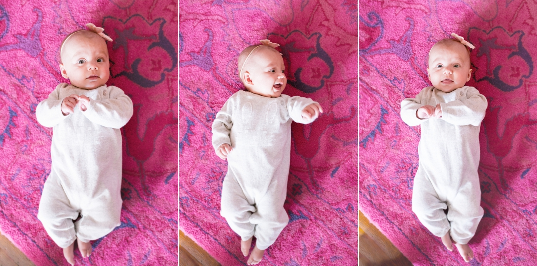 Expressive and playful baby girl on hot pink rug