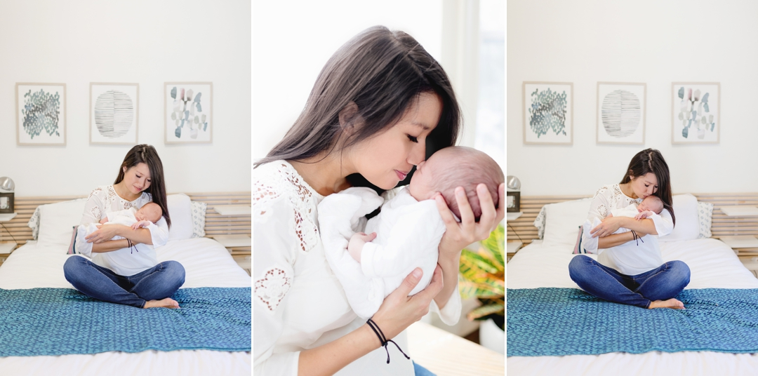 Mother holding and kissing her newborn baby