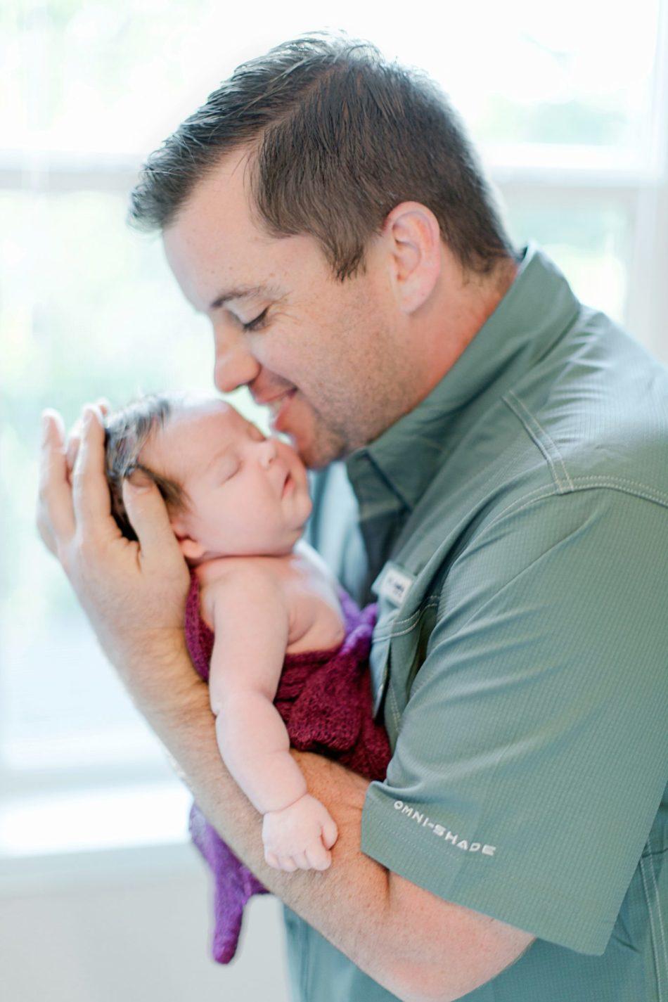 Dad holding newborn baby for in-home newborn portraits